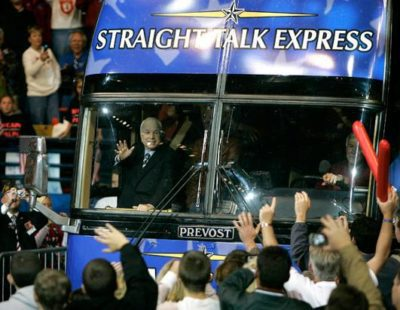 """McCain waves to supporters through the windshield of his """"Straight Talk Express"""" during the 2000 presidential primary"""
