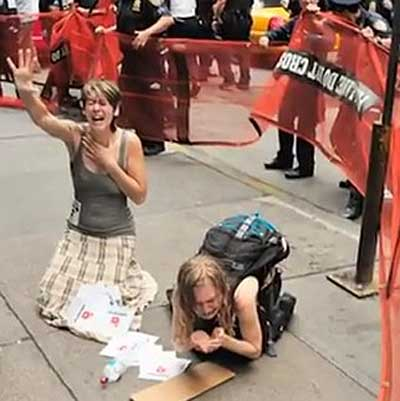 Women inside a protective enclosure, pepper-sprayed by police